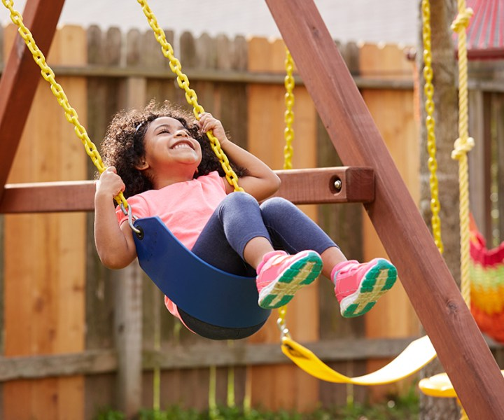 Kid toddler girl swinging on a playground swing in the backyard