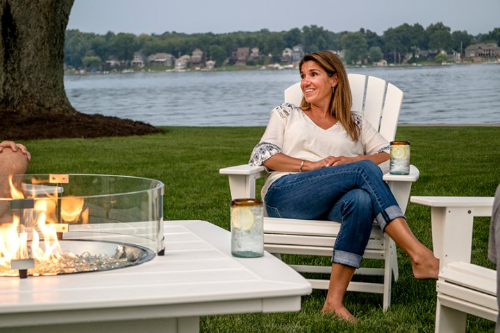 woman sitting on white adirondack chair with lack in background