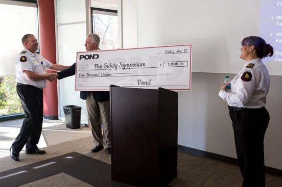 Dwayne Garriss and Karla Richter receive a donation from Pond's Chris Butts.