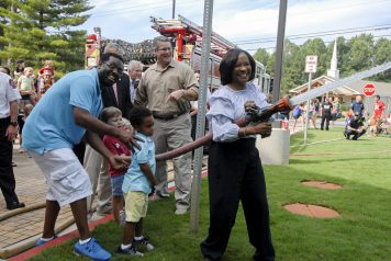 """Deputy County Manager Dr. Jackie McMorris smiles during the ceremonial """"uncoupling of the hose""""."""