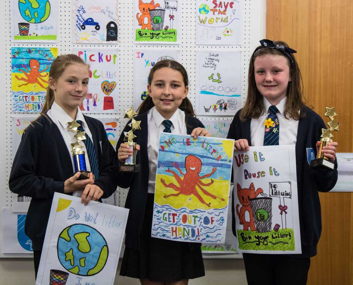 Three girls from Carleton Park school hold up their winning posters