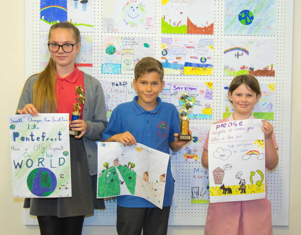 Three pupils from St Giles school hold up their winning posters