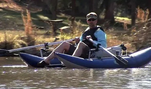fisherman steering a highly rated inflatable pontoon boat for fishing