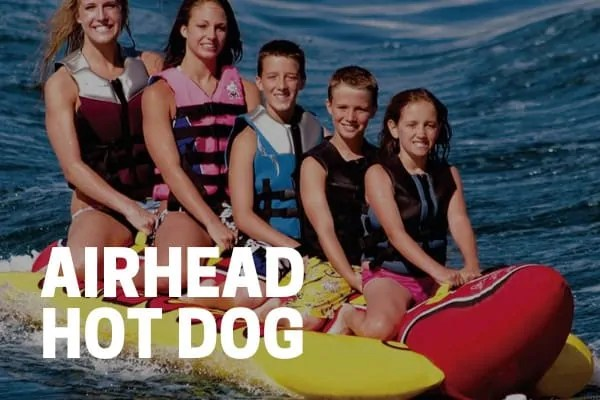 kids and adults riding on an airhead hot dog towable tube