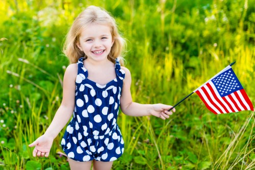 Smiling little girl with long curly blond hair holding american flag and waving it outdoor portrait on sunny day in summer park. Independence Day Flag Day concept