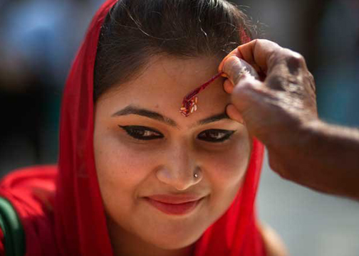 Pandit apply kumkuma on the woman's forehead in temples