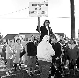 "November 1960: Demonstrators during school integration in New Orleans, Louisiana; one holding sign that reads, ""Integration is A Mortal Sin."""