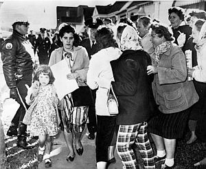 Nov 30, 1960: White parent Mrs. James Gabrielle, with police escort, is harassed by protestors as she walks her young daughter home after day in the newly integrated William Frantz school in New Orleans. Crowd wanted total white boycott. AP photo.