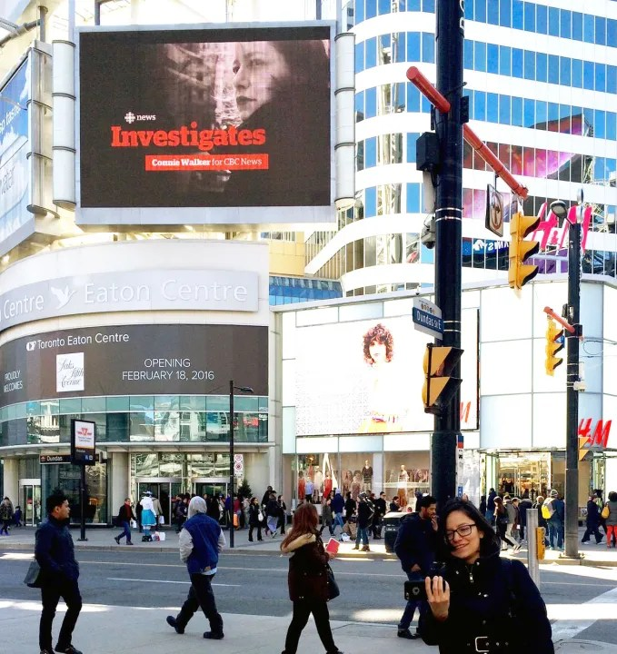 Connie Walker takes a photo of herself in front of a downtown Toronto ad, featuring her image as part of the CBC Investigates team (Facebook)