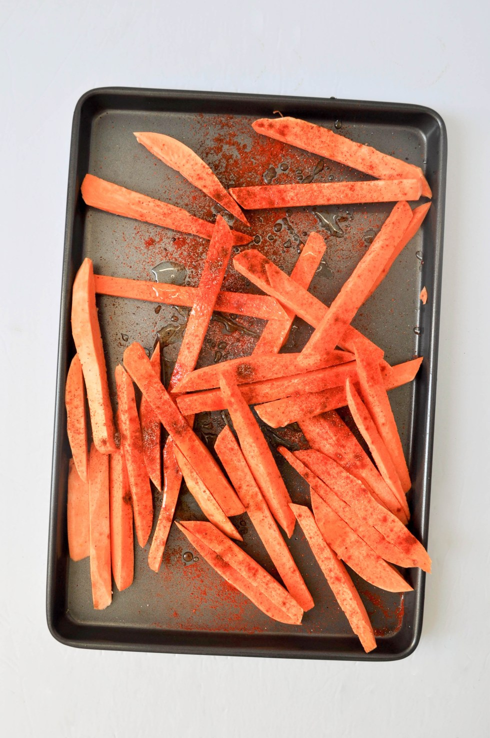 These baked spicy sweet potato fries are tossed with smoked paprika, cayenne and maple syrup and crisped up in the oven | POP KITCHEN