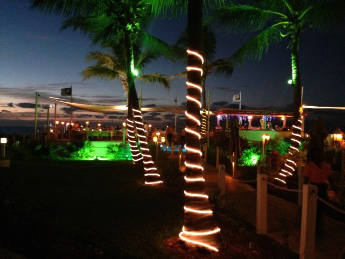 Mango Reef is festive at night with lit palm trees and a deck that extends out over the sand
