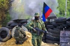 Miliziano a un posto di blocco, da cui spunta la bandiera della Repubblica del popolo di Donetsk.