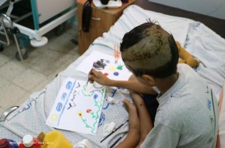 Khaled Shalat (dieci anni) disegna sul suo letto d'ospedale. Una bomba ha colpito la sua casa. Lui, tre fratelli e la madre sono stati feriti. Il padre è morto.