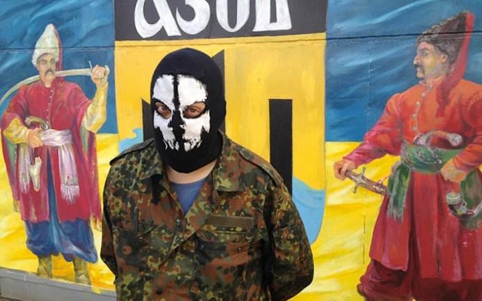 Miliziano del battaglione Azov davanti alla bandiera dell'unità paramilitare.