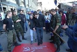 Lviv. Militanti di Pravy Sektor incoraggiano i passanti a calpestare la bandiera comunista.