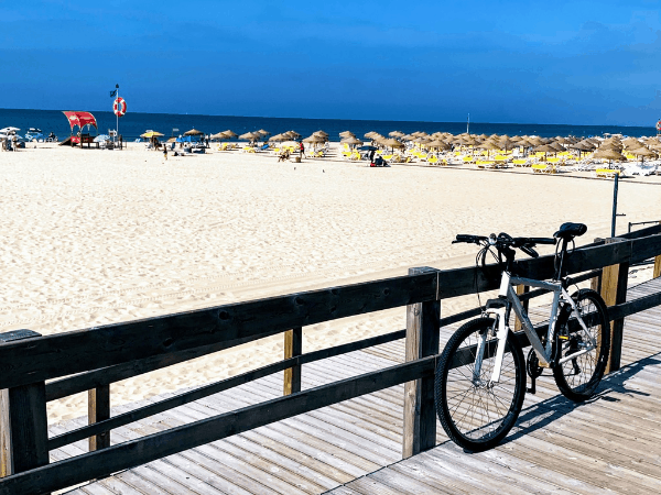 A bicycle parked along a wooden boardwalk with a beach full of umbrellas in the background