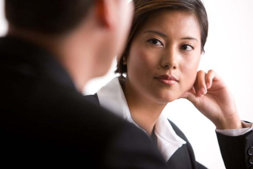 Mentoring woman leaning her face on her hand and listening to her coworker