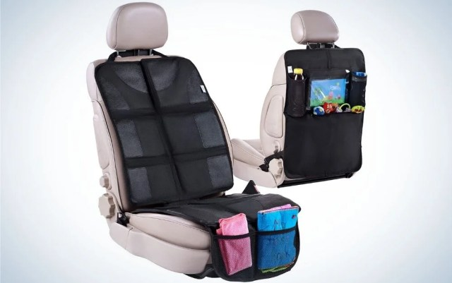 Two beige car seat with black covers in front of them and toys and pads at back of them.