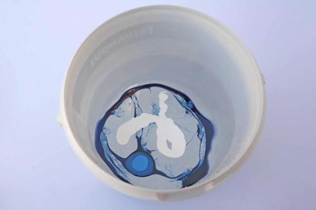 Lacas de unas de diferentes colores vertidas en un recipiente con agua