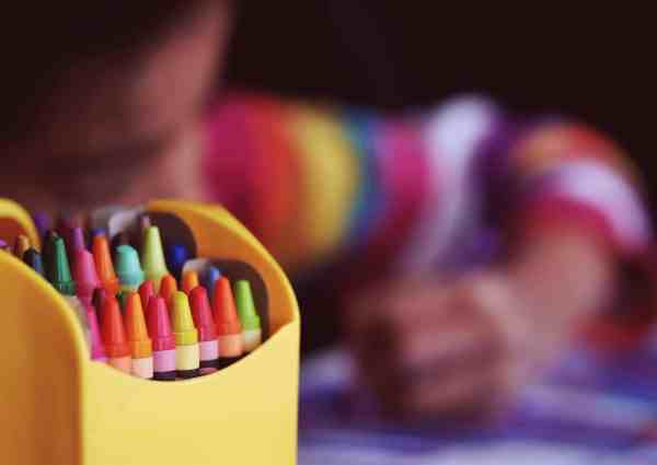 Un niño dibuja con pinturas de cera