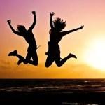 Chicas saltando en la playa al atardecer, felices por viajar con poco presupuesto.