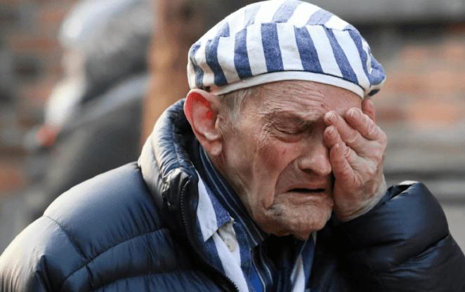 Sobrevivente do holocausto chora em Auschwitz.