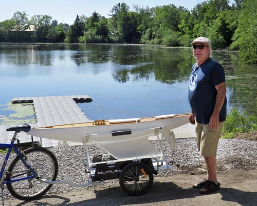 Robin Hitchon uses a bike and trailer to move his recently refurbished scale model J Class sailboat to Silver Lake for water trials.