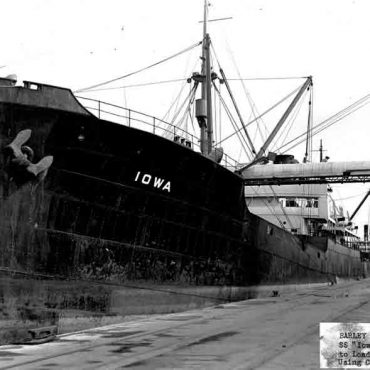 A large ship being loaded by conveyor belts.
