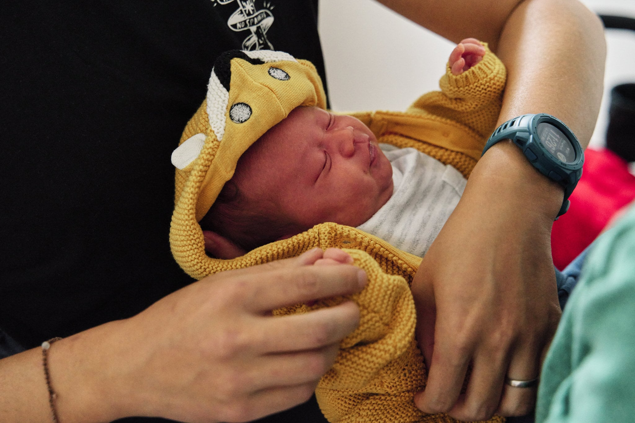 Close up of baby being dressed to go out during a documentary newborn photography session in BRomley.