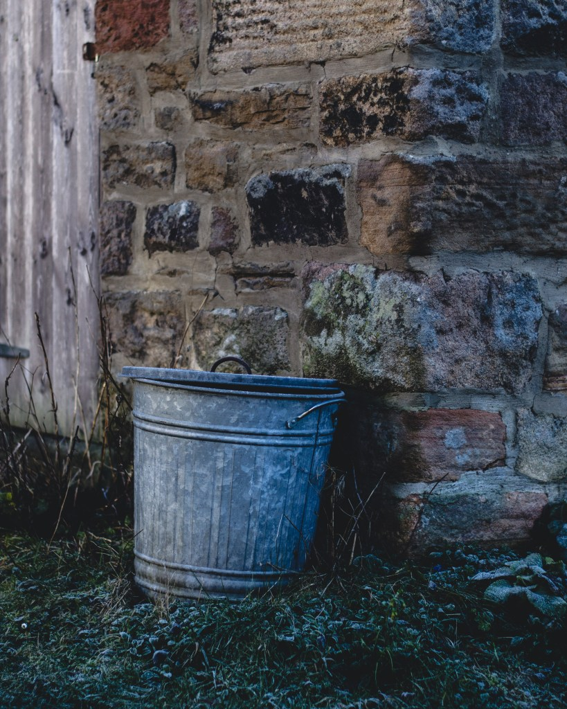 galvanised bin against stone wall in Hathersage