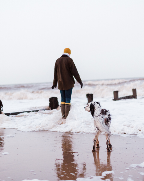 man standing on shoreline wearing wellies and yellow socks with English Setter in foreground