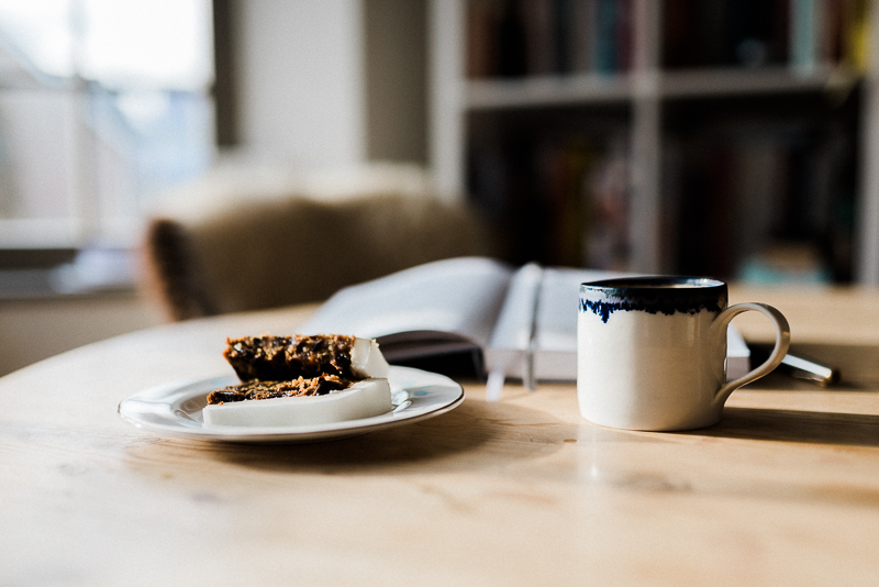christmas cake and a pretty cup of coffee on a pine table