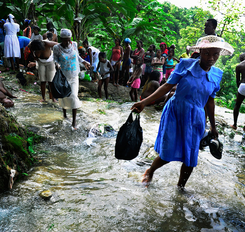 (C)Stanley Greene / NOORIMAGES Ville Bonheur, Saut Deau, Haiti. July 2010. A young girl in blue dress with a white bonnet hat Crossing the cleansing stream at Saut d'Eau