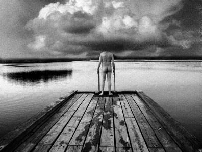 Une homme nu contemple la mer sur un ponton.