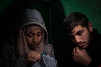 """Ouafe sows one the few pants she owns next to Mohamed in the tent that has become their home. """"We had nowhere to go until a woman gave us this tent"""" says Ouafe, """"people help us """". """"It's cold"""", Mohamed says in a broken English. He can only speak Arabic and Kurdish. He grew up in Tartus with his parents and five siblings.When I ask Ouafe what Mohamed told her about the war in Syria, she becomes grave and silent. """"He was shot in the leg once, and that's the reason it sometimes hurts""""."""