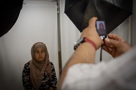 When she arrived here, police took all her documentation. Now, she needs proof of their identity in order to be accepted back into the CETI. She has her portrait taken at a local store in Melilla.