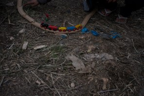 """Ouafe plays with a model train track in the camp. One of her friends has found it in the trash, with other children toys. Not a lot happens during the day, and any new thing they discover is a way to make time go by faster. """"In Rabaat, I was always with my friénds"""", she reminesces, """"We would usually go to my house and spend the afternoon on Facebook or Youtube. On Saturdays, I would escape to watch some concerts. I love American punk music. I had two piercings, one upper lip piercing and another in my nose, which I did with a friend!"""" she remembers, laughing."""