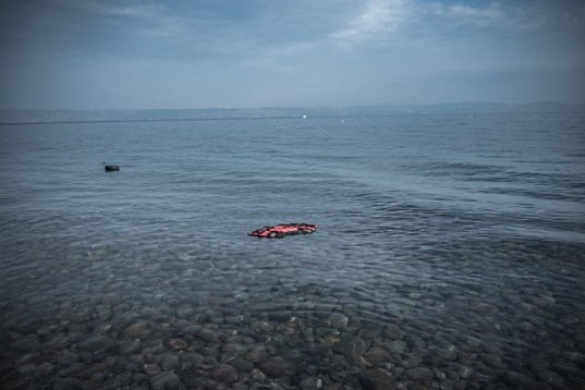 A plastic lifejacket floating near the shore after a dinghy arrived with refugees and migrants on the Greek island of Lesbos after crossing the Aegean sea from Turkey on October 21, 2015.