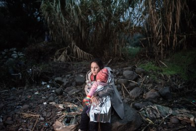 A woman waits on the beach with her child, shortly after arriving, with other refugees and migrants, on the Greek Island of Lesbos, on October 22, 2015 after crossing the Aegean sea from Turkey. An EU scheme to relocate asylum seekers from overstretched Italy and Greece could grind to a halt just two weeks after it began if member states fail to meet their obligations, an EU source said.
