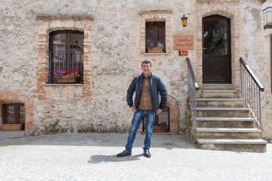 Bairan, 49, posing in front of the restaurant that helped to restructure. He is the immigrant with the longest presence in the small Calabrian town. He landed in 1998 along with 200 other Kurds just in front of the coast of Riace Marina.