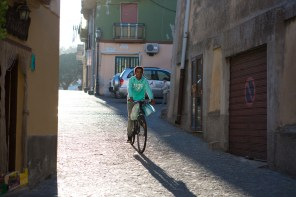 An Eritrean boy carrying groceries on his bike through the streets of Riace.