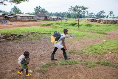 Christine with her little sister carrying heavy water tanks on their backs. Girls in Africa too often miss childhood. Bakumba, Cameroon. 2014