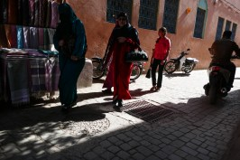 Shadows and lights in a street of Marrakesh. Two women pass next to a seller of scarves and veils.
