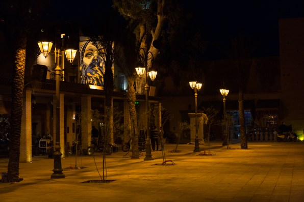 Graffiti of a woman's face with a chador, on a wall hidden by lanterns and trees in a small square in Marrakech.