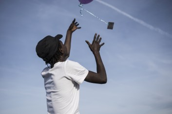 Calais, North of France, 25 October 2015. Arafat, from South Sudan, throwing a balloon with a message in the air, outside his tent in the Jungle of Calais.