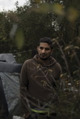 Calais, North of France, 9 November 2015. Ali, from Pakistan, standing next to his tent in the Jungle refugee camp. His frustration and worries about living in the Jungle were reaching the limit when I met him, therefore he was considering traveling to another