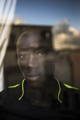 Milazzo, South Italy, 22 September 2015. Abdullah, from Senegal, at the window of his room. He lives in a flat shared with other young asylum seekers, as part of the SPRAR system, which grants protection to refugees and asylum seekers.