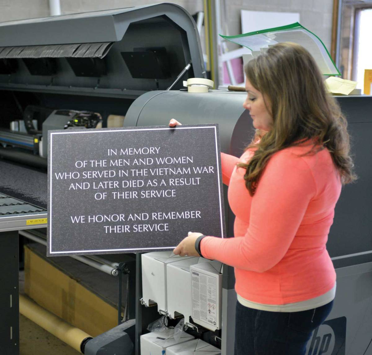 Rosemarie Breske Garvey shows one of many panels being printed at Blooming Color via a specialty application on aluminum sheets for an special tribute to 11 men from Naperville who gave the ultimate sacrifice, an addition to the Vietnam Memorial Wall. The replica of the wall is being created as the nation remembers the 50th anniversary since the Vietnam War began. PN Photo / Tim Penick