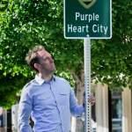 Joe Noriel with the Purple Heart City sign at Putnam Plaza on Petaluma Blvd, Photo Argus Courier