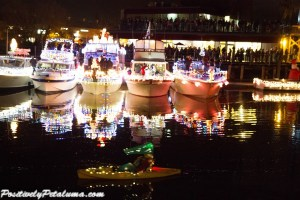 Small Paddle Boat Glides By Lighted Boats